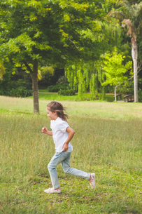 Side view of a young girl running at parkの写真素材 [FYI00001245]
