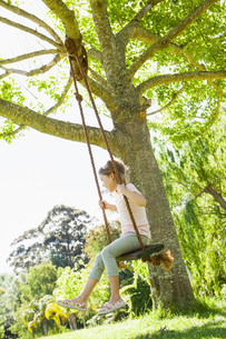 Young girl sitting on swing at parkの写真素材 [FYI00001248]