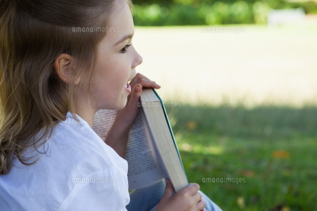 Close-up of young girl reading book in parkの写真素材 [FYI00001250]
