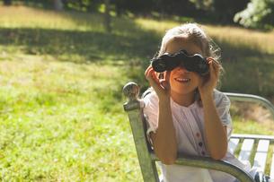 Girl looking through binoculars at parkの写真素材 [FYI00001254]