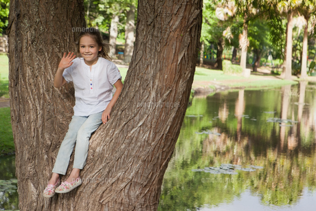 Portrait of a smiling girl sitting on tree at parkの写真素材 [FYI00001256]
