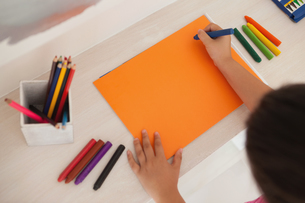 High angle of a girl drawing on orange paper at homeの写真素材 [FYI00001258]