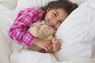 Smiling girl with stuffed toy resting in bedの写真素材 [FYI00001259]