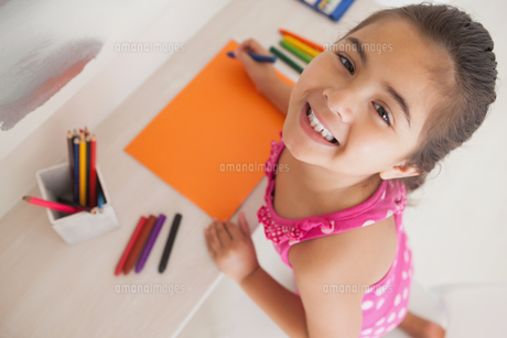 Young girl drawing on orange paperの写真素材 [FYI00001261]