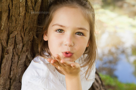 Close-up of a girl blowing a kiss at parkの写真素材 [FYI00001262]
