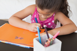 Young girl drawing on orange paperの写真素材 [FYI00001263]