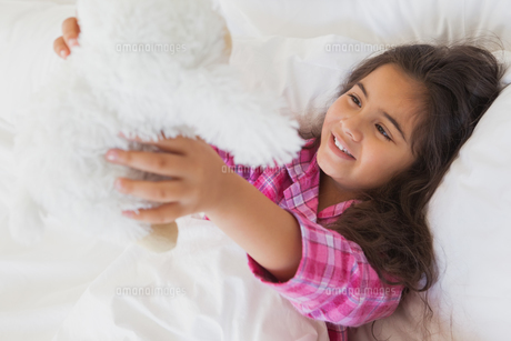 Smiling girl with stuffed toy resting in bedの写真素材 [FYI00001264]