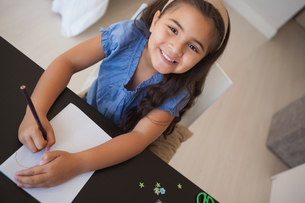 Portrait of a young smiling girl drawing on tableの写真素材 [FYI00001267]