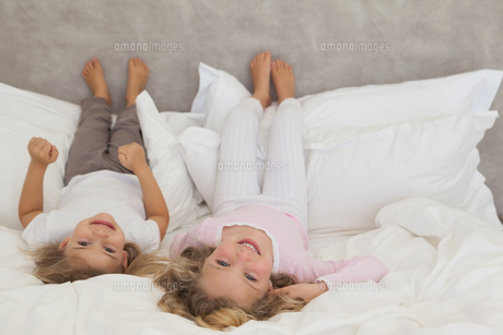 Portrait of two smiling kids lying in bedの素材 [FYI00001277]