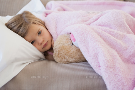 Young girl resting on sofa with stuffed toyの写真素材 [FYI00001280]