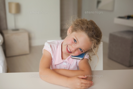 Smiling young girl using mobile phoneの写真素材 [FYI00001281]
