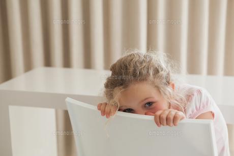 Cute girl hiding face behind chairの写真素材 [FYI00001282]