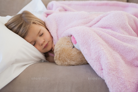 Close-up of a girl sleeping on sofa with stuffed toyの写真素材 [FYI00001283]