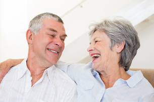 Retired couple sitting on couch smiling at each otherの写真素材 [FYI00001291]