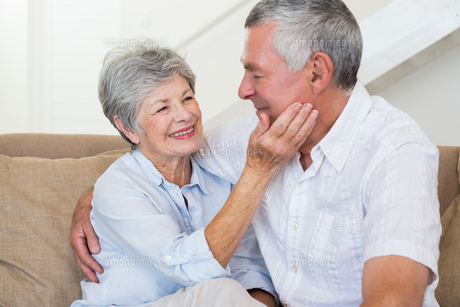 Affectionate retired couple sitting on the sofaの写真素材 [FYI00001296]