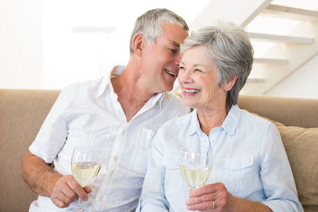 Senior couple sitting on couch drinking white wineの写真素材 [FYI00001298]