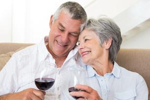 Senior couple sitting on sofa having glasses of red wineの素材 [FYI00001299]