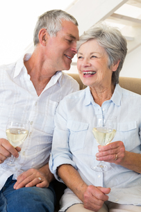 Senior couple sitting on couch drinking white wineの写真素材 [FYI00001308]