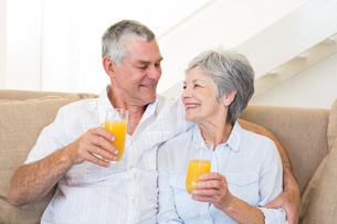 Senior couple sitting on couch drinking orange juiceの写真素材 [FYI00001309]