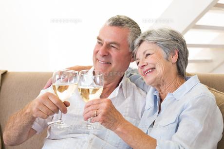 Senior couple sitting on couch having white wineの写真素材 [FYI00001311]