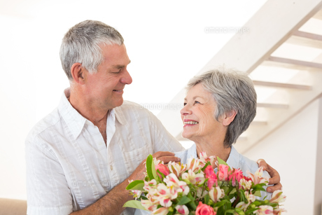 Senior couple smiling at each other holding bouquet of flowersの写真素材 [FYI00001319]