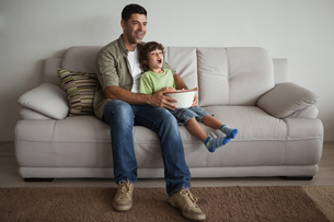 Father and son with popcorn bowl watching tv in the living roomの写真素材 [FYI00001320]