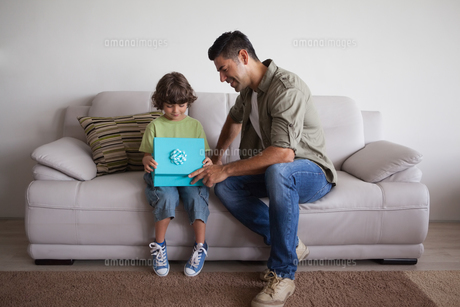 Father and son with gift box sitting in living roomの写真素材 [FYI00001323]