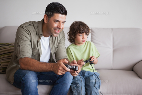 Father and son playing video games in living roomの写真素材 [FYI00001324]