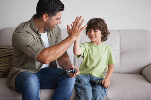 Father and son playing video games in living roomの写真素材 [FYI00001325]