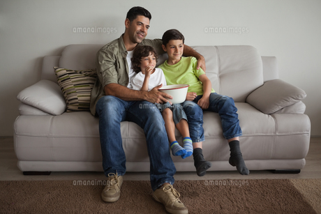 Father and sons with popcorn bowl watching tv in the living roomの写真素材 [FYI00001327]