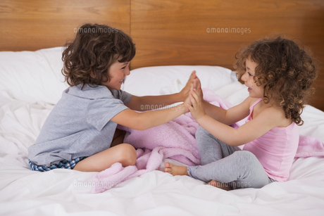 Siblings clapping hands in bedの写真素材 [FYI00001331]