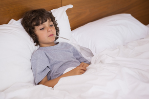 Sick child with thermometer resting in bedの写真素材 [FYI00001332]