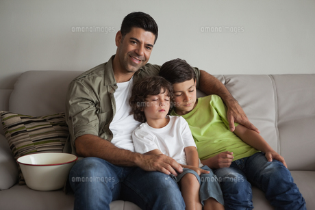 Father and sleepy sons with popcorn bowl watching tv in living roomの写真素材 [FYI00001334]