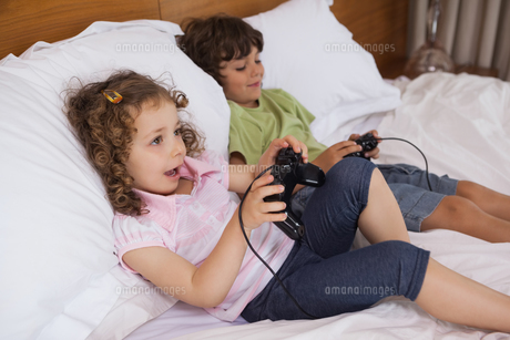 Brother and sister playing video games in bedroomの写真素材 [FYI00001337]