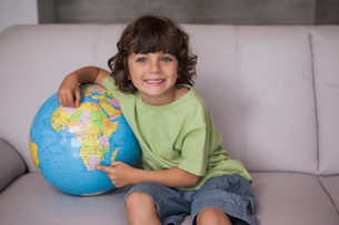 Portrait of a happy kid with globe in living roomの写真素材 [FYI00001338]