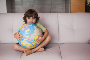 Portrait of a happy kid with globe in the living roomの写真素材 [FYI00001340]