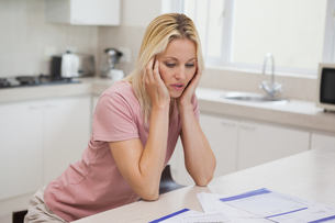 Unhappy woman with sitting in kitchenの写真素材 [FYI00001341]