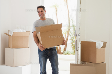 Smiling man carrying boxes in new houseの写真素材 [FYI00001342]