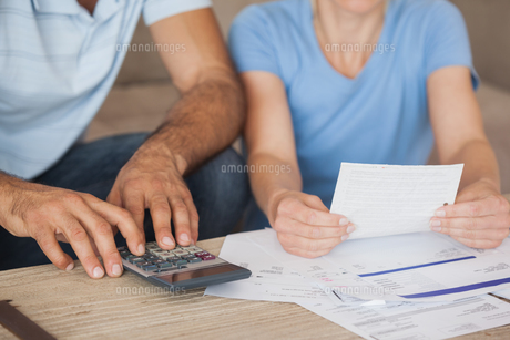 Mid section of a couple with bills and calculatorの写真素材 [FYI00001349]