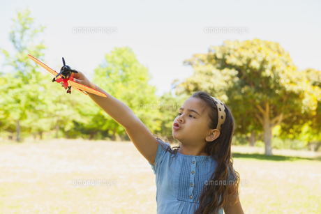 Girl playing with a toy plane at parkの写真素材 [FYI00001354]