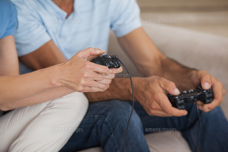 Close-up mid section of couple playing video gamesの写真素材 [FYI00001355]