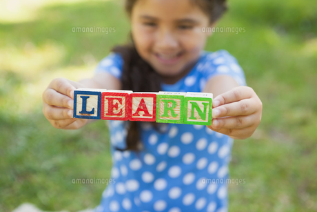 Happy girl holding block alphabets as learn at parkの写真素材 [FYI00001360]