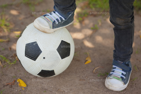Low section of boy with leg on football at parkの写真素材 [FYI00001362]