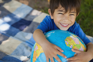 Close-up portrait of a cute boy holding globeの写真素材 [FYI00001366]