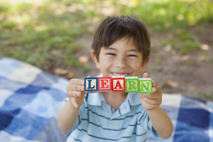 Happy boy holding block alphabets as learn at parkの写真素材 [FYI00001367]