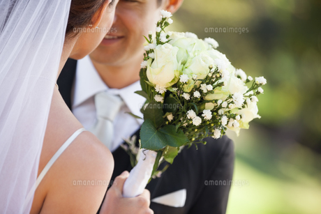 Mid section of a newlywed couple with bouquet in parkの写真素材 [FYI00001373]