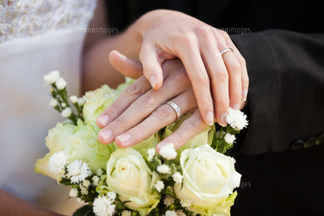 Newlywed couple with wedding rings and bouquetの写真素材 [FYI00001375]