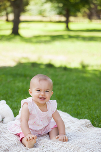 Cute baby sitting on blanket at parkの写真素材 [FYI00001377]