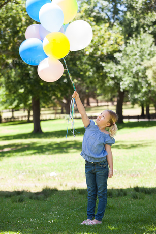 Young girl with colorful balloons at parkの写真素材 [FYI00001380]