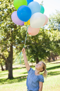 Young girl with colorful balloons at parkの写真素材 [FYI00001381]